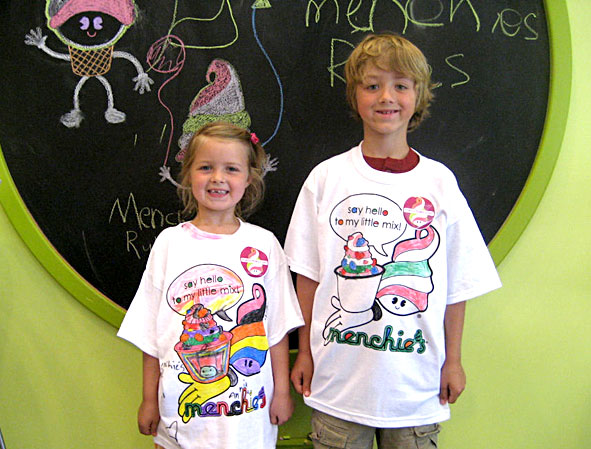 Two kids stand in front of a chalkboard inside Menchie's.