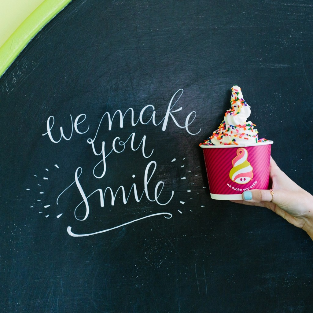 "A blackboard with ""We make you smile"" written next to a hand holding a cup of frozen yogurt"