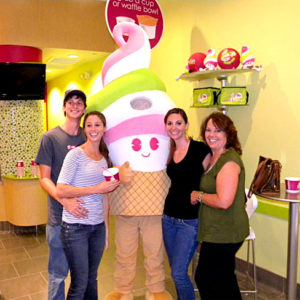 Four smiling customers flank a Menchie's mascot inside a Menchie's store.