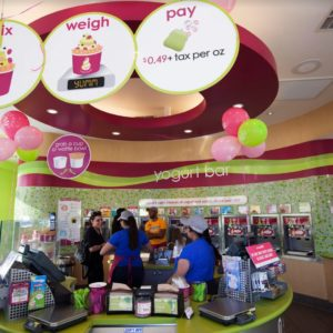 Menchie's workers behind the circular counter help talk with customers against a backdrop of the curved wall of frozen yogurt dispensers.