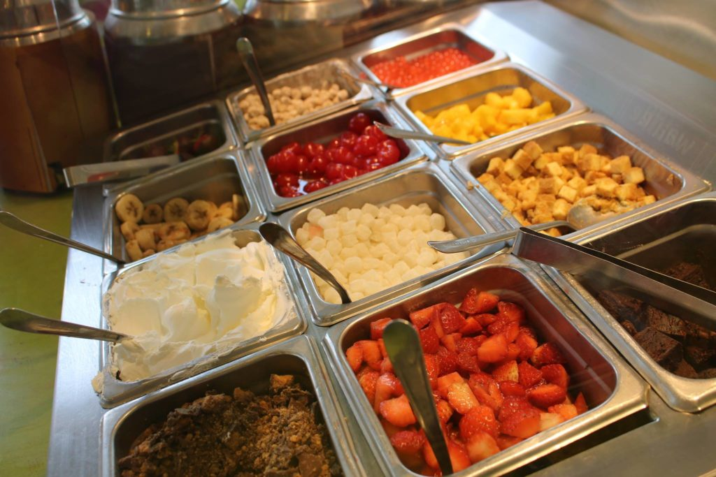 A cafeteria-style serving bar shows bins of toppings including fruit, cake bites and whipped cream.