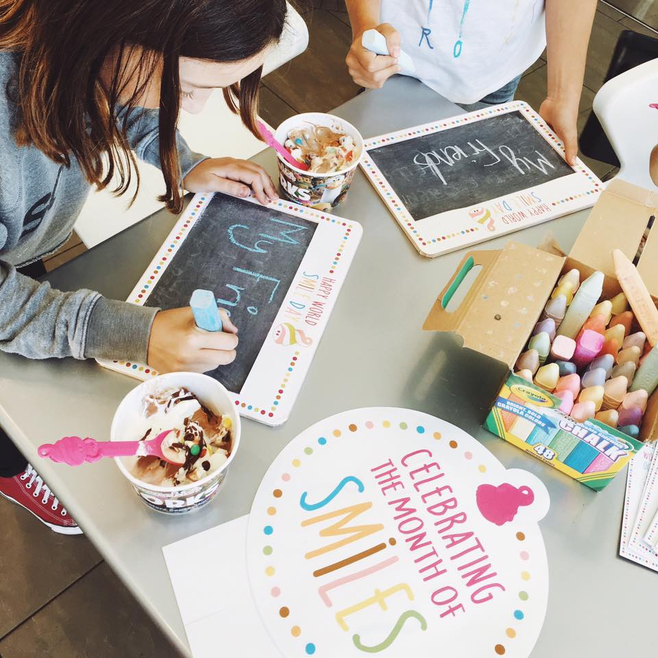 Two little girls write the words 'My friends' on small chalkboards at a table with their half-eaten cups of frozen yogurt beside them.
