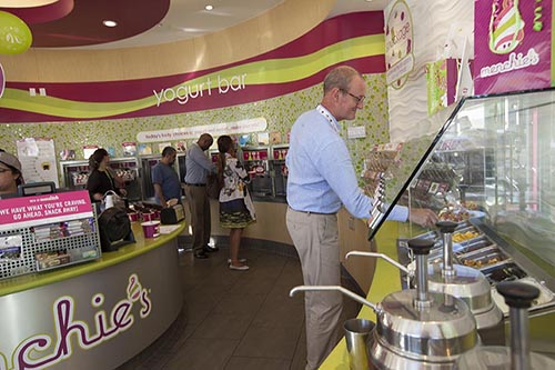 A guest selects toppings to put on his Menchie's frozen yogurt.