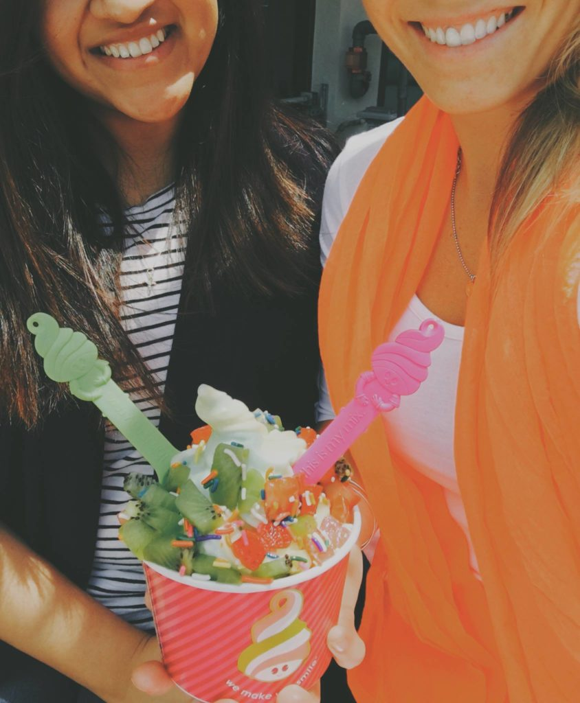 Two girls hold a cup of frozen yogurt topped with kiwi and rainbow sprinkles.