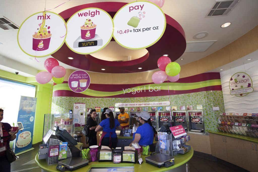 Menchie's employees help guests weigh and pay for their frozen yogurt.